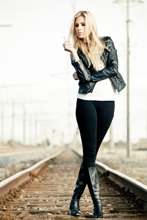 hand rails: Young woman standing on a railroad and smoking Stock Photo