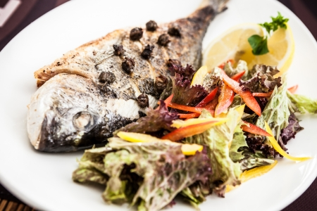 Grilled gilt-head bream fish in herbs and lemon photo