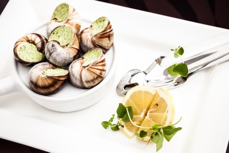 Escargots with garlic butter and lemon Stock Photo