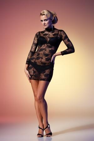 tacones negros: Jovencita morena con vestido negro posando sobre fondo de colores Foto de archivo