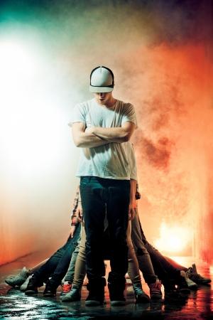 baile hip hop: Brakedancer chico adolescente de pie en una cortina de humo con las piernas detr�s de muchos