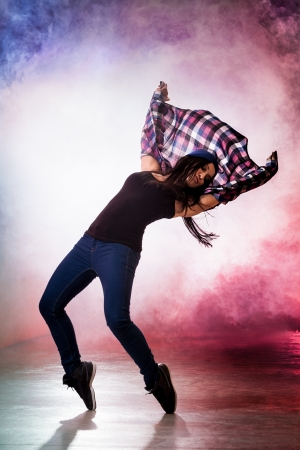 Teenage brakedancer girl in passionate dance pose with smoke on background photo
