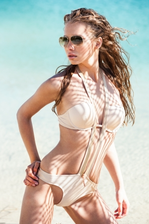 wet suit: Young woman on a beach in bikini and sunglasses