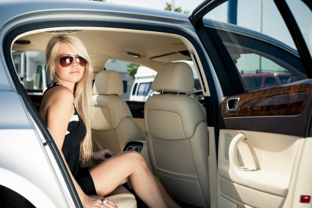 Young blond lady sitting on a backseat of a luxury car photo