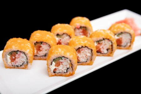 california roll: California roll served on a plate isolated on black