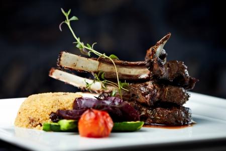 costilla: Carre de cordero a la parrilla con ensalada tibia cuscús, verduras asadas, mostaza Dijon y salsa de vino tinto Foto de archivo