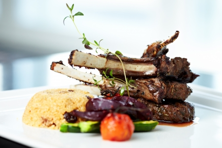 Grilled lamb carre with warm couscous salad, roasted vegetables, Dijon mustard and red wine sauce photo