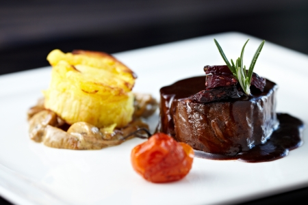 Roasted beef tenderloin with herb-potato muffin, mushroom ragout, baked tomatoes and rosemary-currant sauce Banque d'images