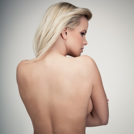 nude back: Young blond lady with a beautiful hair on gray background