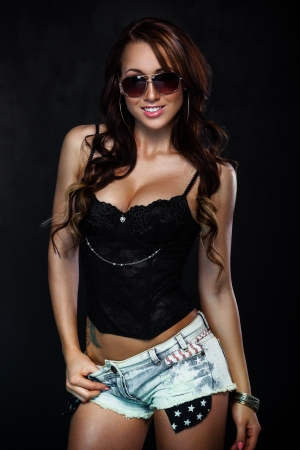 sexy woman lingerie: Sexy woman in sunglasses posing on dark background Stock Photo