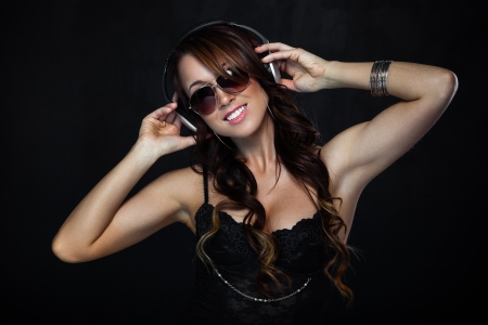 Sexy woman in sunglasses listening for the music using headphones photo