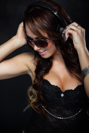 Sexy woman in sunglasses listening for the music using headphones Stock Photo