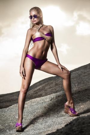 Young lady in bikini standing on sand rocks