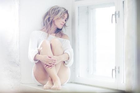 Beautiful lady sitting by the window Stock Photo
