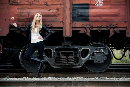 hand rails: Young woman standing near a train