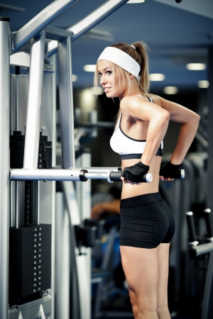 Smiling athletic woman pumping up muscles in a gym photo