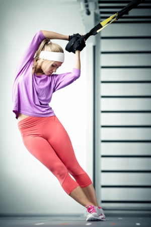 Young woman streching muscles TRX training photo