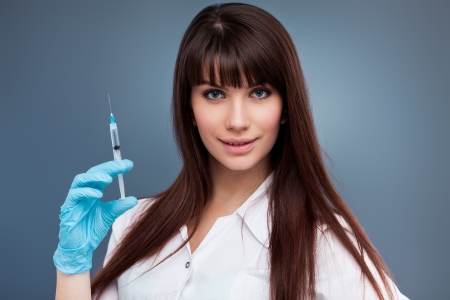 sexy female doctor: Sexy rse holding syringe on blue