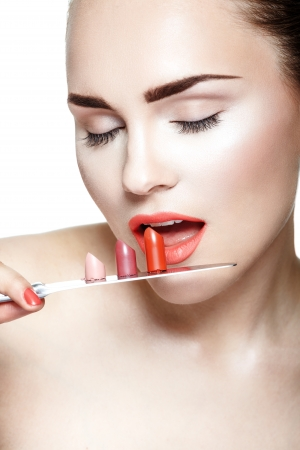 holding a knife: Portrait of a young woman holding knife with a lipstick on white