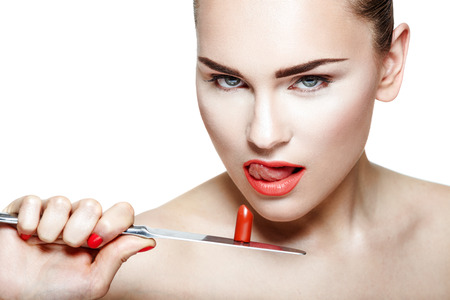 woman knife: Portrait of a young woman holding knife with a lipstick on white