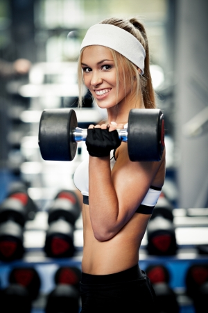 Smiling athletic woman pumping up biceps in a gym photo