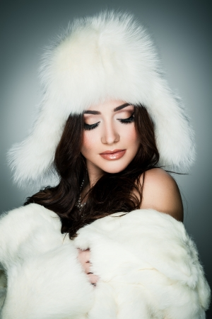Young brunette lady in white fur hat posing on grey background photo