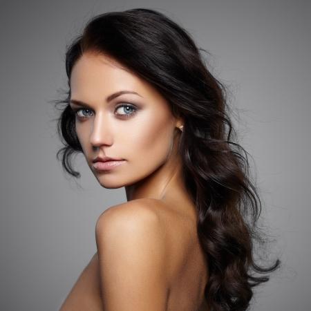modelo desnuda: Retrato de la hermosa modelo femenino sobre fondo gris