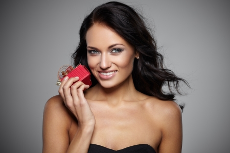 Smiling young woman holding a gift in a red box on grey background photo