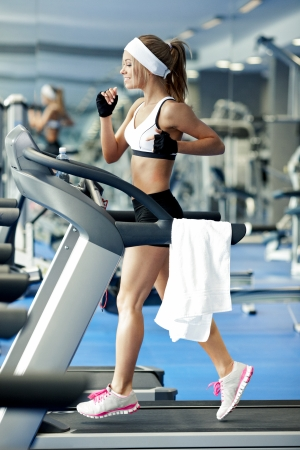water aerobics: Smiling athletic woman running on a treadmill