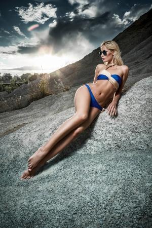 Jonge dame in bikini liggend op zand rotsen