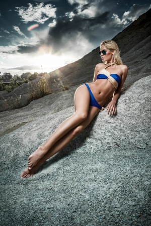 Young lady in bikini lying on sand rocks