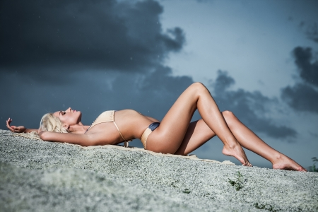 Young lady in bikini lying on sand rocks photo