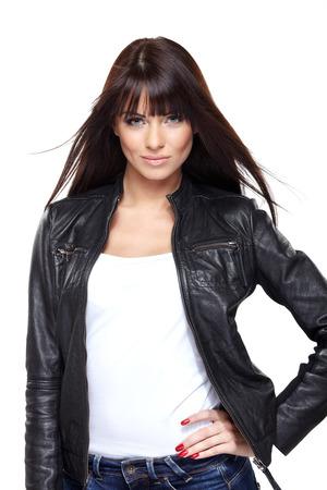 Betoverende jonge vrouw in zwart lederen jas op een witte achtergrond