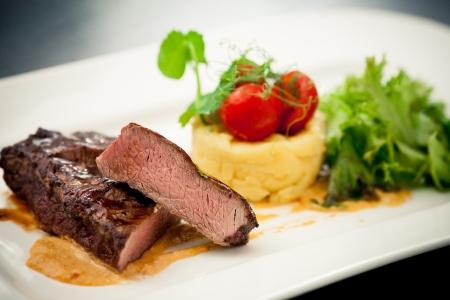 Gegrilde entrecôte met hummus, spek, room en pruimensaus en aardappelpuree