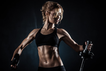 Brutal athletic woman pumping up muscules with barbell Stock Photo - 25821284