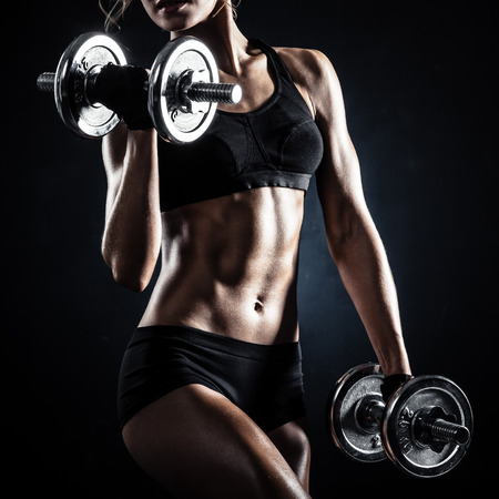 athletic body: Brutal athletic woman pumping up muscules with dumbbells Stock Photo