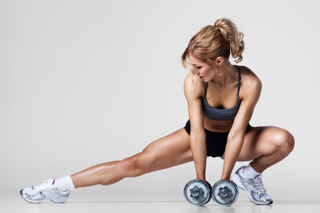 female body: Smiling athletic woman pumping up muscules with dumbbells and stretching legs