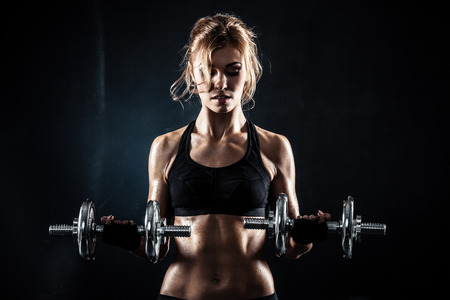 fit: Brutal athletic woman pumping up muscules with dumbbells Stock Photo