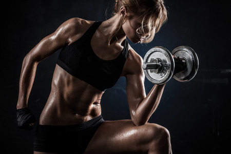 bodybuilding: Brutal athletic woman pumping up muscules with dumbbells Stock Photo