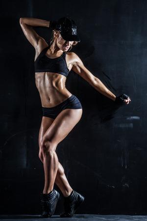 Sexy woman in a cap posing on dark Banco de Imagens - 25824675
