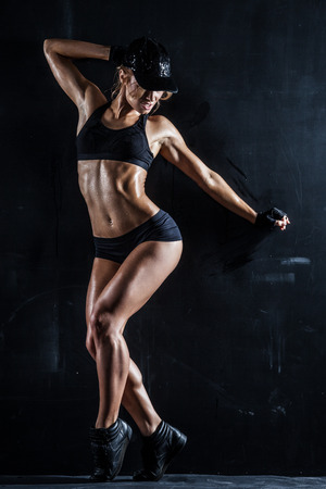 Sexy woman in a cap posing on dark Stock Photo - 25824675