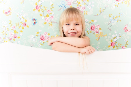 Little adorable girl with a sly smile standing behind a bed photo
