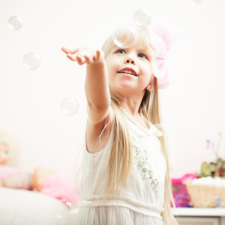 Little adorable girl playing with soap bubbles photo