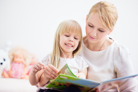 Mother and daughter reading a colorful book at home photo