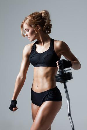 Lachende atletische vrouw oppompen muscules met halter op een grijze achtergrond