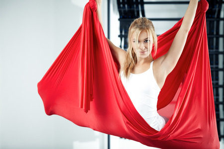 Young woman making antigravity yoga exercises photo