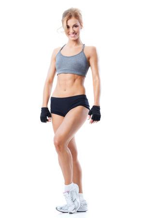 Lächelnde sportliche Frau mit sportlichen Outfit auf weißem Lizenzfreie Bilder