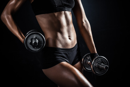 violence in sports: Brutal athletic woman pumping up muscules with dumbbells Stock Photo