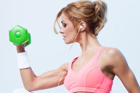 Smiling athletic woman pumping up muscules with dumbbells on gray background Standard-Bild