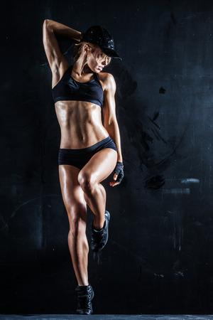 Sexy Frau in einer Kappe posiert auf dunklem Lizenzfreie Bilder